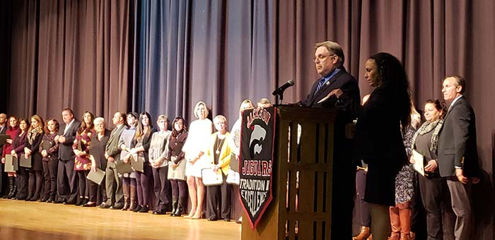 Jackson Board of Education President John Burnetsky (at podium) joins Board Vice President Sharon Dey in naming the 2019 Teachers of the Year and Educational Services Professional of the Year who are standing on the Jackson Memorial High School Fine Arts Auditorium stage. (Photo by Bob Vosseller)