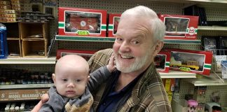 Frank Gustafson holds his 6-month-old grandson Grayson Weiss, who came for a visit during the last day of operation of his grandfather's store, the Jackson Hobby Shop. (Photo by Bob Vosseller)
