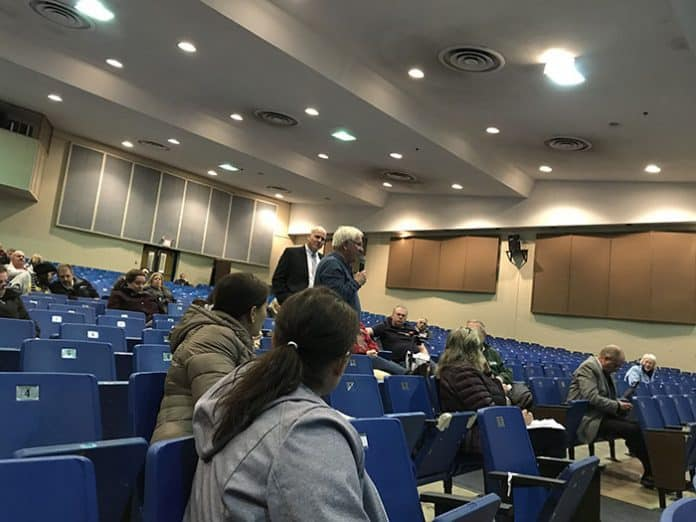 A resident asks about the reduction in state aid, as Superintendent David Healy brings the microphone to audience members. (Photo by Chris Lundy)