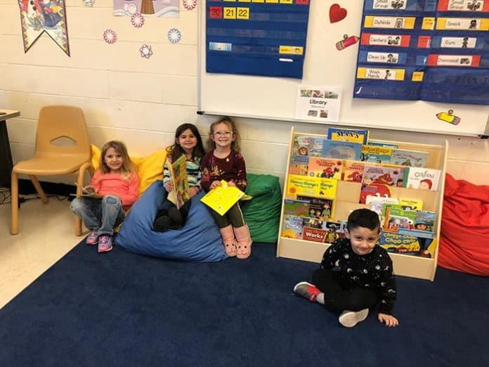 A group of preschoolers sits together and works on their reading skills at Cecil S. Collins. (Photo by Kimberly Bosco)