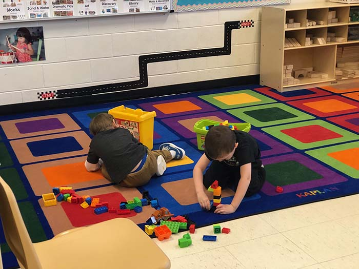 Two preschool students are focused on creating with building blocks before heading into nap time. (Photo by Kimberly Bosco)