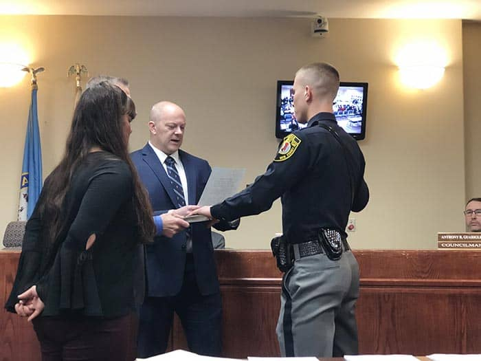 Officer Zach Wiatrowski was sworn in by Mayor Gregory Myhre, surrounded by his parents. (Photo by Kimberly Bosco)