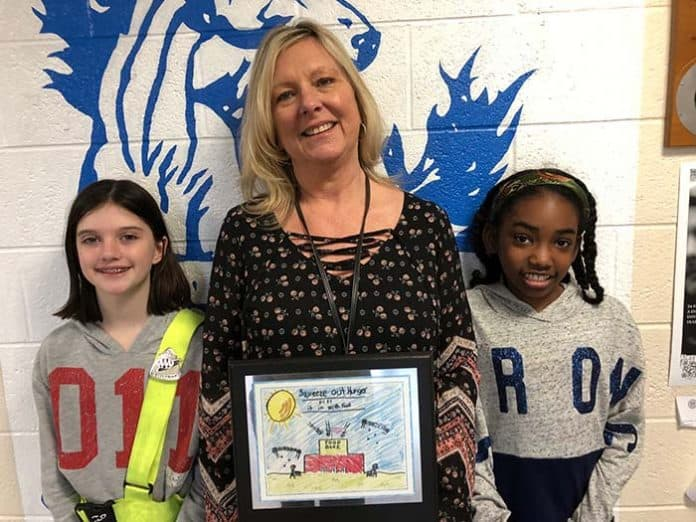 Lanes Mill Elementary School 5th Grade teacher Sharon Panek poses with contest winners. For essay, Michaela Smith (on left) and for drawing, Kianna Thompson (on right). (Photo by Judy Smestad-Nunn)