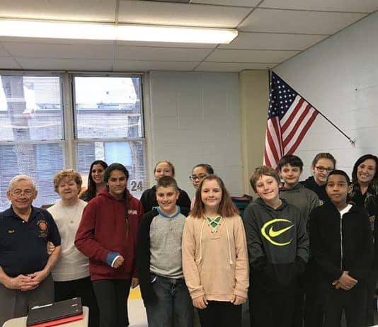 Dina Nagy's sixth grade class poses beneath their new flag with Bob and Darlene Scheiderman and Superintendent Loren Fuhring. (Photo by Chris Lundy)