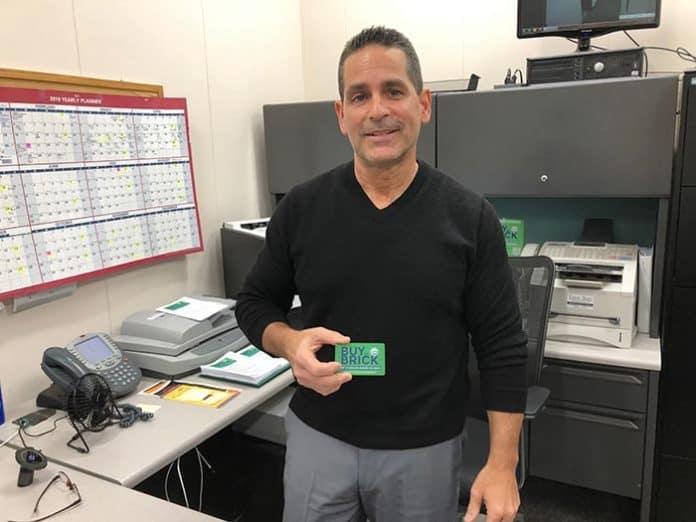 Darren Sirota shows off a Buy in Brick card. (Photo by Judy Smestad-Nunn)