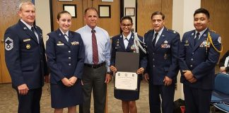 Board member Thomas Colucci (third from left) joins Air Force Major Michael Macagnone, far left and Senior Master Sgt. Charles Latimer (second from right) in recognizing the district's ROTC Unit. Holding the certificate is Cadet Hannah Mahabir. (Photo by Bob Vosseller)