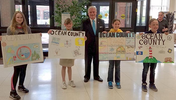 Ocean County Clerk Scott M. Colabella poses with the poster contest winners. (Photo courtesy Ocean County)