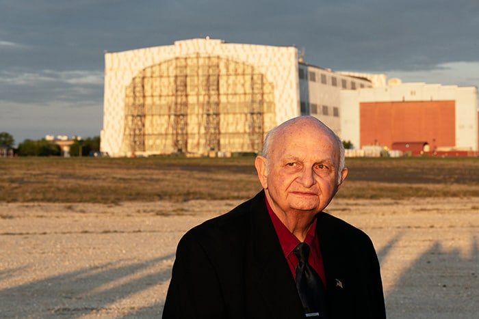 Carl Jablonski, Navy Lakehurst Historical Society president, stands with Hangar One in the background. (Photo by Jennifer Peacock)