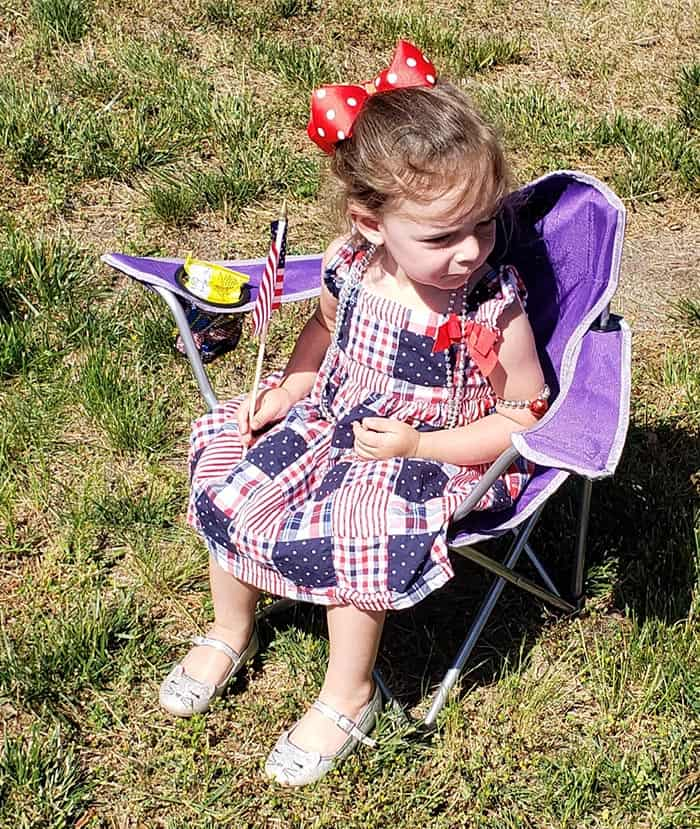 Little Avery Lafontaine, 2, of Jackson sits in comfort during this year's Memorial Day Parade where she joined four other members of her family including her grandmother Janet Fitzpatrick. (Photo by Bob Vosseller)