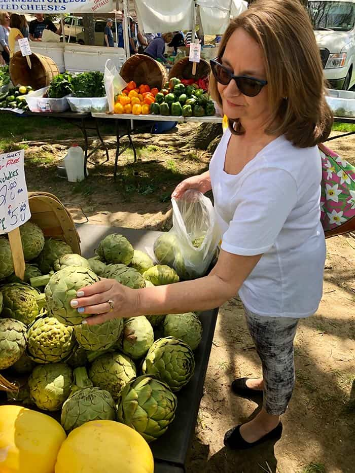Gina Bonomo of Herbertsville shops the artichokes. (Photo by Judy Smestad-Nunn)