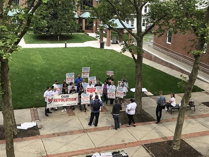 Medicare For All protestors met up before the town hall, and held signs throughout it. (Photo by Chris Lundy)