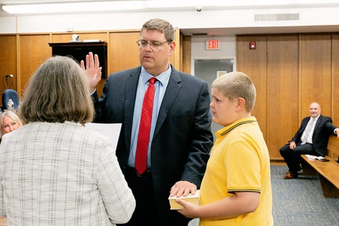 Robert Hudak, with his son Michael holding the family Bible, was sworn in as councilman by clerk Marie Key on May 28. (Photo by Jennifer Peacock)