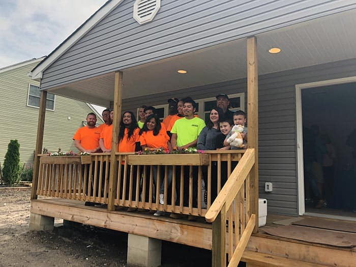 Shaunna Smith and her sons, RJ and Raymond, join members from Habitat for Humanity and OCVTS at the House Dedication Ceremony on June 13. (Photo by Kimberly Bosco)