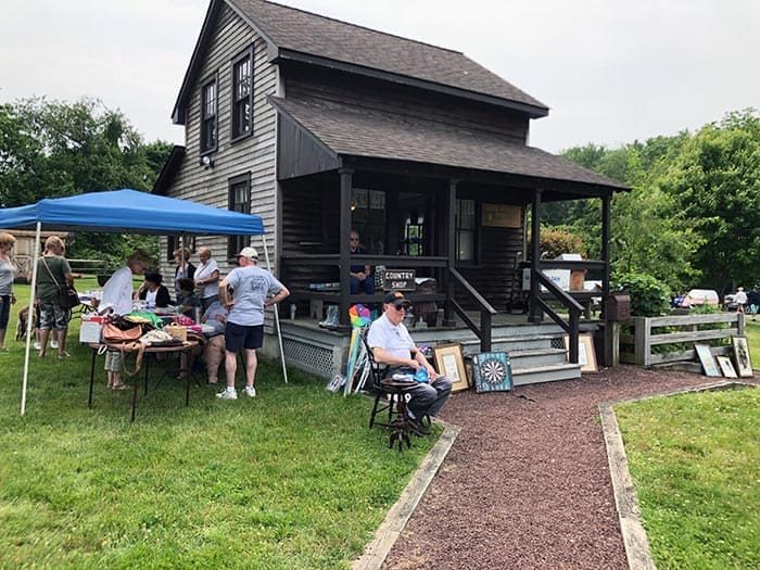 "Historical Society President Ed Mangold sells memberships in front of the Lizzie Herbert House, a ""country shop"" located next to the homestead. (Photo by Judy Smestad-Nunn)"
