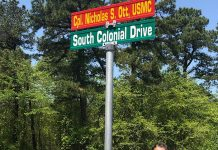 """Rory Dunckley stands at a road sign that will soon read """"Hawk's Way."""" (Photo courtesy Rory Dunckley)"""