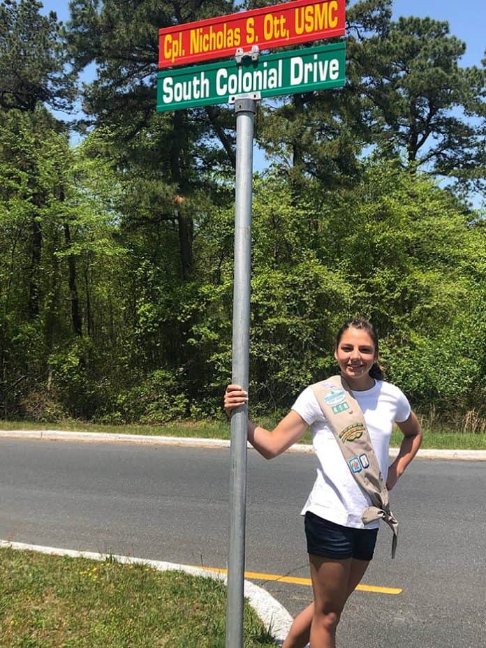 "Rory Dunckley stands at a road sign that will soon read ""Hawk's Way."" (Photo courtesy Rory Dunckley)"