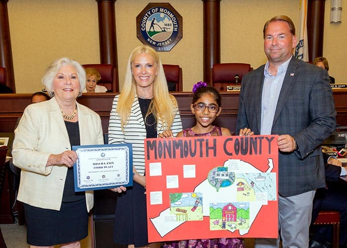 Third place winner Mischa Jain of Indian Hill School (Holmdel) with, from left to right, Surrogate Rosemarie D. Peters, Clerk Christine Giordano Hanlon and Sheriff Shaun Golden. (Photo courtesy Monmouth County)