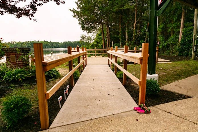 The red cedar fencing has brass plaques that bear the names of servicemembers who have died. The borough is looking to add the names of those who are currently serving or have served and are still living. (Photo by Jennifer Peacock)